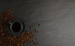 Top view espresso cup and coffee beans on black stone background with copy space. White coffeecup or mug with hot beverage