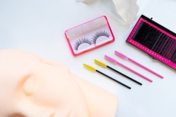 Top view Eyelash extension tools on white background, brush lash comb, Micro Eyelash Brushes Mascara Wan, fake eyelashes and Silicone Mannequin Head