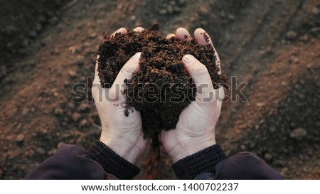 Top view: Farmer holding soil in hands close-up. Male hands touching soil on the field. Farmer is checking soil quality before sowing wheat. #1400702237