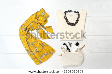 Top view fashion female outfit layout with trendy chain print: yellow skirt, sweater, jewelry, bag glasses makeup flash drive on white background. lifestyle concept. Flat lay. Elegance pattern. #1308010528