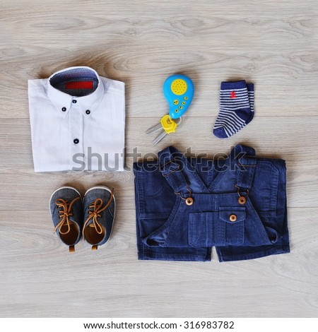 Top view fashion trendy look of baby clothes and toy on the wooden floor, baby fashion concept. Little boy clothes set.
