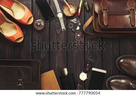 Top view, fashionable male and female personal items with space on a dark wooden background. Leather bag, shoes, watches, stylish accessories. #777790054