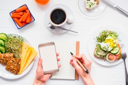 Top view Female hands holding smart phone and writing in notebook on served white wooden table with breakfast dishes. Day diet planning and healthy eating concept. Selective focus, copy space
