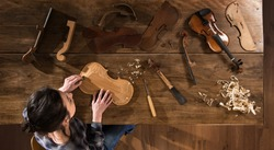 Top view. Female luthier working on the creation of a violin. She sits at a wooden table in her workshop, various tools and instrument are placed on the workbench