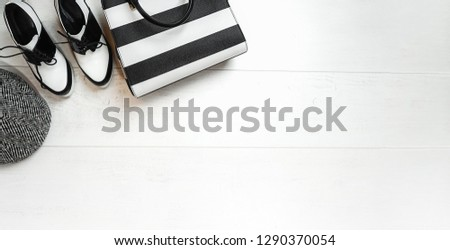 Top view female outfit collection dress: black and white shoes cap bag accessories on white wooden background. Valentine's Day Spring Autumn lifestyle collections. Flat lay, copy space, horizontal.