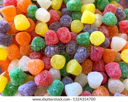 top view flat lay background bright red, yellow and yellow Natural Fruit gum drops coated in granulated sugar