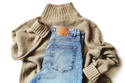 Top view flat lay composition fashion photography. Brown woolen sweater and trendy blue jeans pants. Online clothes shopping