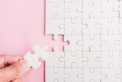 Top view flat lay of hand-holding last piece white paper jigsaw puzzle game last pieces put to place for solve problem complete mission, studio shot on a pink background, quiz calculation concept