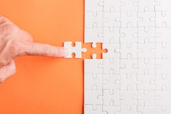 Top view flat lay of hand-holding last piece white paper jigsaw puzzle game last pieces put to place for solve problem complete mission, studio shot on an orange background, quiz calculation concept
