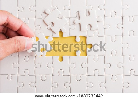 Top view flat lay of hand-holding last piece white paper jigsaw puzzle game last pieces put to place for solve problem complete mission, studio shot on a yellow background, quiz calculation concept Stockfoto ©