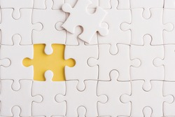 Top view flat lay of paper plain white jigsaw puzzle game texture incomplete or missing piece, studio shot on a yellow background, quiz calculation concept