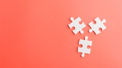 Top view flat lay of three paper plain white jigsaw puzzle game last pieces for solve, studio shot on a red background, quiz calculation concept