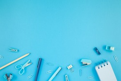Top view flat lay of workspace desk styled design school and office supplies with copy space turquoise blue color paper background minimal style. Template for feminine blog social media