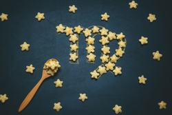 top view flat lay virgo horoscope sign made from crispy corn stars on a black background