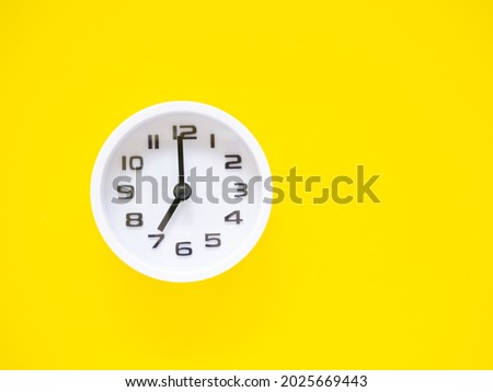 Top view, Flat lay, white clock show time at 7 o'clock on office yellow workplace tabletop. Copy space for your text. Business and education concept.  Foto stock ©