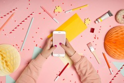 Top view flat lay with hands with smartphone mockup with empty screen on bright pink background. Creative celebration concept. Confetti, paper garland, party accessories and  decorations composition.