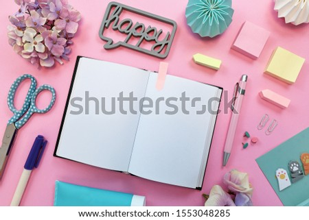 Top view flat lay with various colorful office supplies like pencils, scissors, notepads, pins and open empty notebook as placeholder for text on pink background