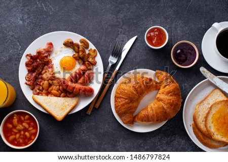 Top view flatlay with classical english breakfast with fried bacon, mushrooms and eggs. Served with orange juice, croissants and black coffee. Stock photo ©