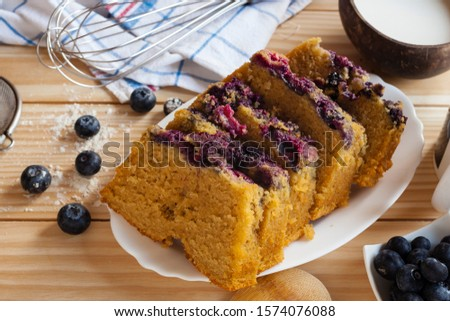 Top view food still life shot of a blue berries cake with lactose free vegetarian coconut milk sliced cake on wooden background with berries, flour,kitchen towel, spoon and strainer. #1574076088
