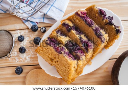 Top view food still life shot of a blue berries cake with lactose free vegetarian coconut milk sliced cake on wooden background with berries, flour,kitchen towel, spoon and strainer. Bakery concept. #1574076100