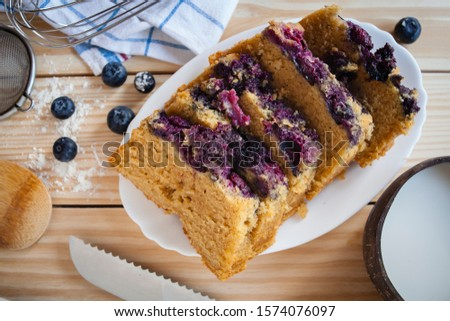 Top view food still life shot of a delicious sweet blue berries cake with lactose free vegetarian coconut milk sliced cake on wooden background with berries, strainer. flour,kitchen towel and knife.  #1574076097