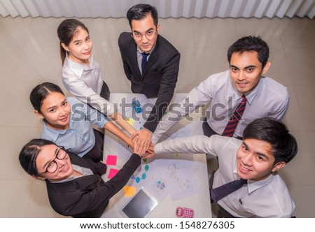 Top view for group of businesspeople putting stacking hands while meeting for showing unity of teamwork. Business and teamwork concept.