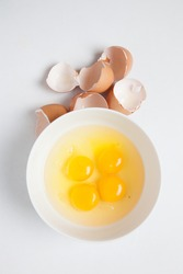 Top view Four egg yolks in white bowl and broken egg shells on white background