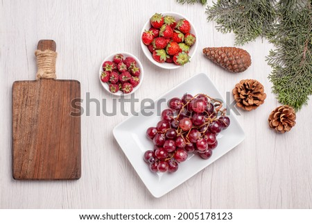 top view fresh grapes with strawberries and raspberries on white desk fruit color juice mellow fresh Foto stock ©