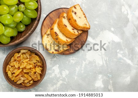 top view fresh green grapes mellow and delicious with cakes on light white desk fruit fresh mellow tropical Foto stock ©
