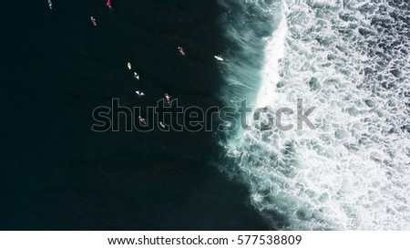 Top view from drone of a group of surfers seek to the ocean to catch next beautiful wave during surf lessons in Bali school. Just came down wave and people floating on surf boards. Background for blog