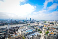 Top view from St. Paul's Cathedral on London, skyscrapers, River Thames and buildings on the background of blue sky