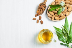 Top view Glass bottle of Almond oil and almond nuts in wooden shovel, almonds with shell in bamboo bowl on white table with green fresh raw almonds on almond tree branch