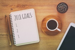 Top view 2018 goals list with notebook, cup of coffee on wooden desk