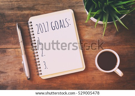 Top view 2017 goals list with notebook, cup of coffee on wooden desk #529005478