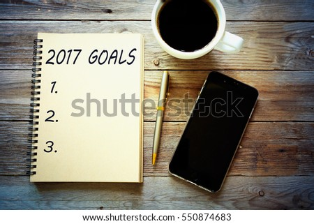 Top view 2017 goals list with notebook, cup of coffee on wooden desk #550874683
