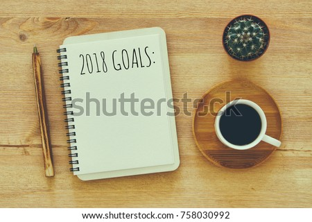 Top view 2018 goals list with notebook, cup of coffee on wooden desk - Shutterstock ID 758030992
