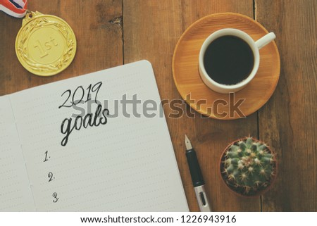 Top view 2019 goals list with notebook, cup of coffee over wooden desk #1226943916
