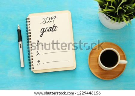 Top view 2019 goals list with notebook, cup of coffee over wooden desk #1229446156