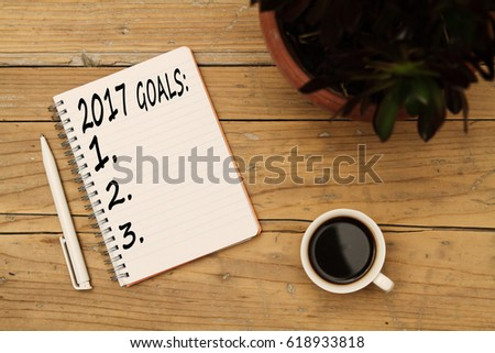 Top view 2017 goals list with notebook, flower, cup of coffee on wooden desk #618933818