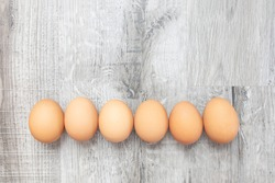 Top view, group of natural organic fresh eggs aligns on light grey wooden texture background. Raw egg, uncooked ingredient for healthy cuisine. Concept and symbol of Easter, fun and happiness holiday.