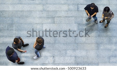 top view group of people are playing and talking with the smart phone on the concrete pedestrian (Aerial top view)