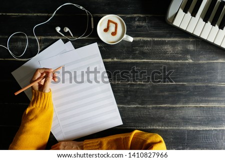 Top view hand of musician holding pencil to compost a song on blank staff notation sheet over black painted wood table with white cup of coffee with musical note symbol on frothy surface and keyboard. ストックフォト ©