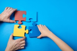 Top view hands of a autistic child and father arranging color puzzle symbol of awareness for autism spectrum disorder. Autism Awareness Day or month.