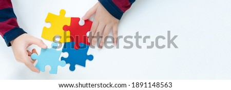 Top view hands of a little child arranging color puzzle symbol of public awareness for autism spectrum disorder. World Autism Awareness Day, ASD, Caring, Speak out, Campaign, Togetherness. Banner.