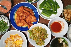 Top view home-cooked food. Malaysian traditional home-cooked meal, crispy chicken, fried bitter gourd with egg, steamed okra and seaweed soup.