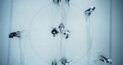 Top View Ice Hockey Rink Arena Game Start: Two Players Face off, Sticks Ready, Referee Ready to Drop the Puck. Intense Game Wide of Competition. Aerial Drone Shot