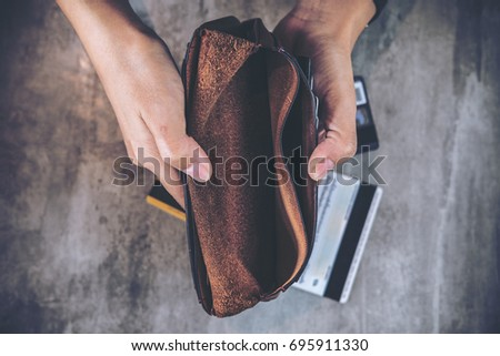 Top view image of a man's hands open an empty leather wallet with credit cards on the table Stock photo ©