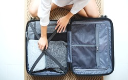 Top view image of a woman packing luggage for a trip