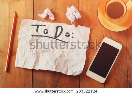top view image of blank paper with the text to do in hand write, next to cellphone and coffee cup over wooden table