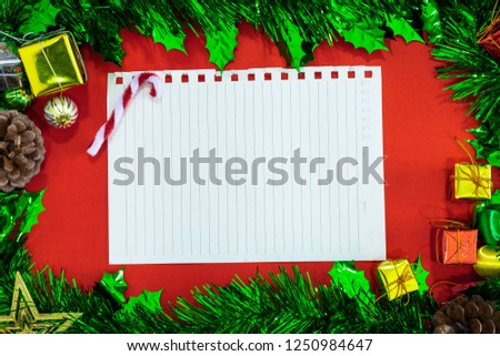 Top view image of Christmas festive decorations with empty notebook and pencil on red paper background, New Year concept.